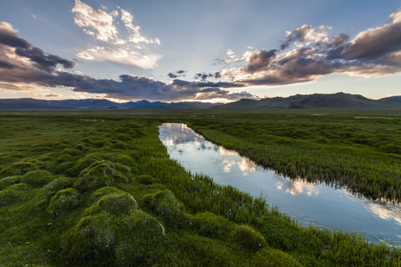 riverbank: Beautiful landscape with river, mountains and cloudy sky. Stock Photo