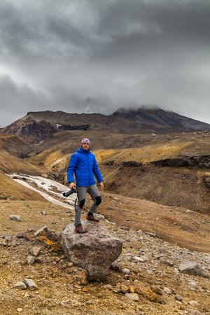 Young photographer on the background of volcanic rocks. Kamchatka.