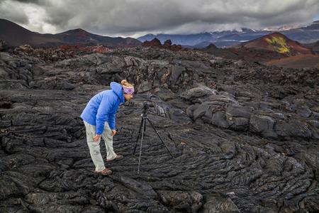 kamchatka: Young photographer on the background of volcanic rocks. Kamchatka.