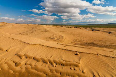 Desert landscape on the background of blue sky and white clouds. Gobi Desert.