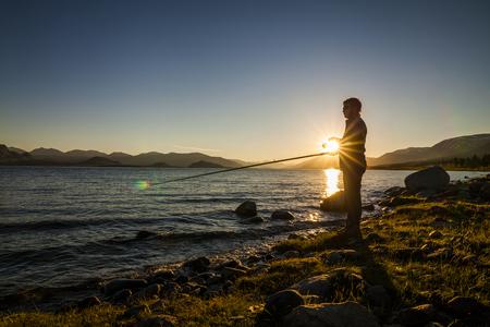 fishingpole: Silhouette of a fisherman at sunset. Fishing on mountain lake