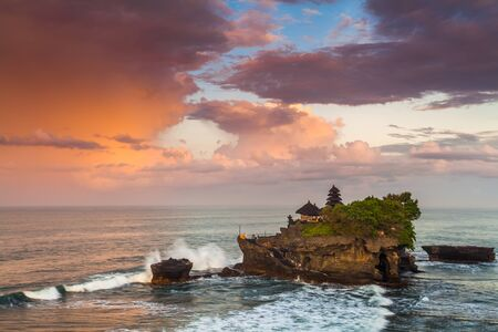 The Pilgrimage Temple of Pura Tanah Lot is perched dramatically on a large coastal rock. Stock Photo