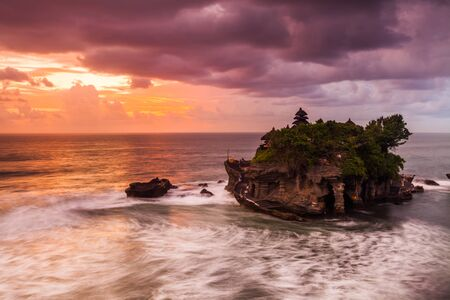 dramatically: The Pilgrimage Temple of Pura Tanah Lot is perched dramatically on a large coastal rock. Stock Photo