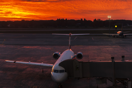 airstrip: Plane at the airport near the terminal at sunset Stock Photo