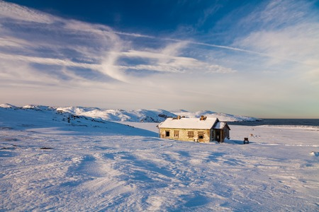 Winter landscape with cabin hut at sunset