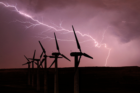 Silhouette of wind turbines on the background of a stormy sky