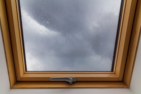rains: New roof window during the rains with drops on the glass Stock Photo