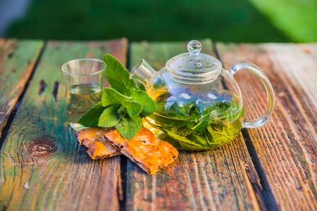 Tea pot of herbal tea on a wooden table.