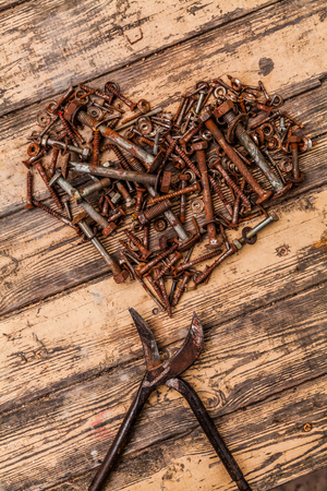 bolts and nuts: Heart of bolts and nuts on a wooden background. Stock Photo