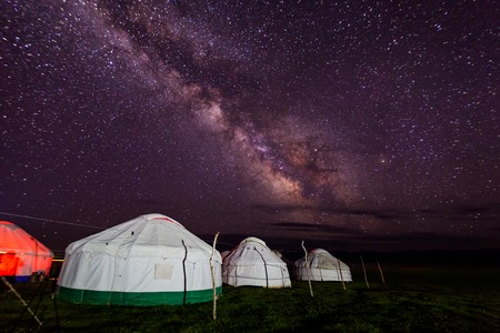 Group of yurts against the starry sky at night in the desert Stockfoto
