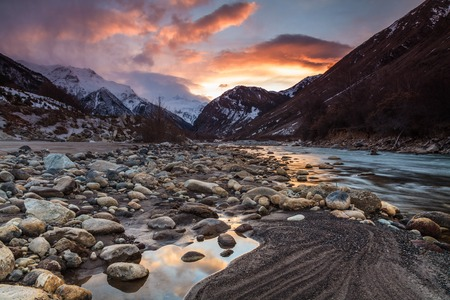 Beautiful sunset in the mountains on the river bank