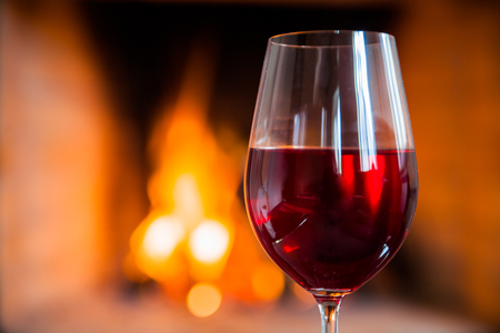 Glasse of red wine on the background of fire.