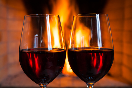 Two glasses of red wine on the background of fire.