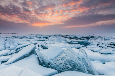 Colorful sunset over the crystal ice of Baikal lake