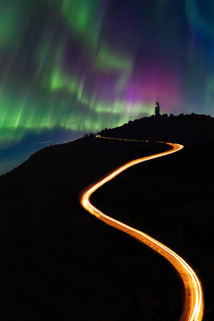 Night road in the mountains against the background of the Northern Lights Stock Photo