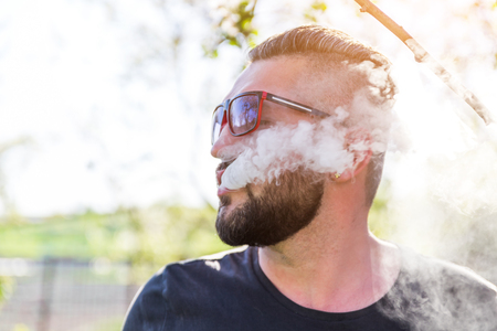 Portrait of young guy with beard in cap and sunglasses vaping an electronic cigarette with puffs of steam at sunset