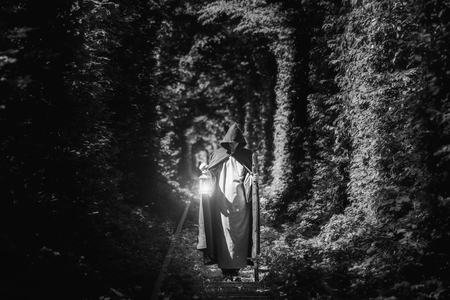 A magician in a cloak in a dark forest with a lantern. Black and white image.