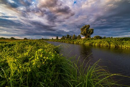 Dramatic clouds over the river at sunset. Banco de Imagens