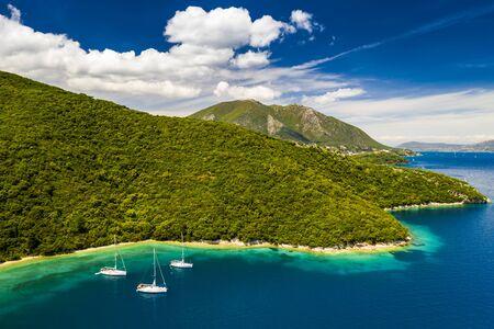 Yachts in the bay near the green island. Summer vacation, Greece, Kefalonia.