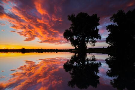 Beautiful clouds at sunset over the lake. Summer landscape.