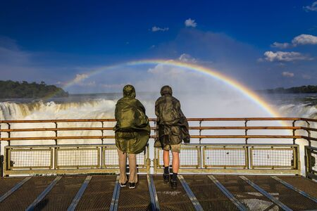 Travelers at Iguazu Falls. View of the rainbow and a waterfall. Argentina.