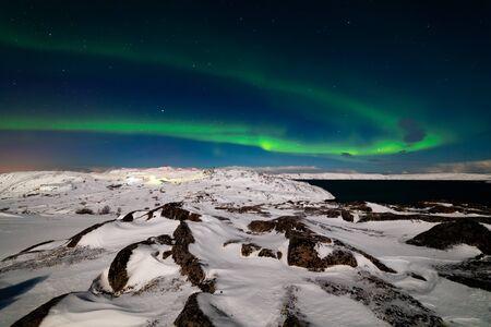 Northern Lights on the shore of the Arctic Ocean. Foto de archivo - 129845928
