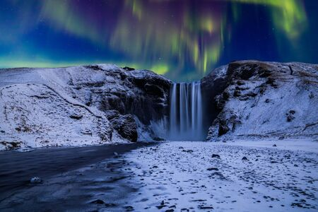 Skogafoss waterfall in the winter at night under the northern lights. Iceland.