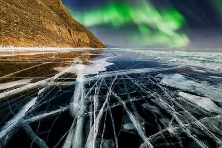 Aurora borealis over frozen lake Baikal in winter