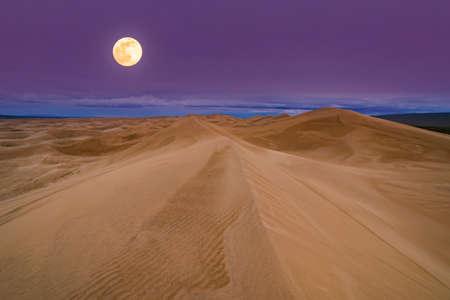 Full moon over the sand dunes in the desert. Arid landscape of the Sahara desert Stock Photo