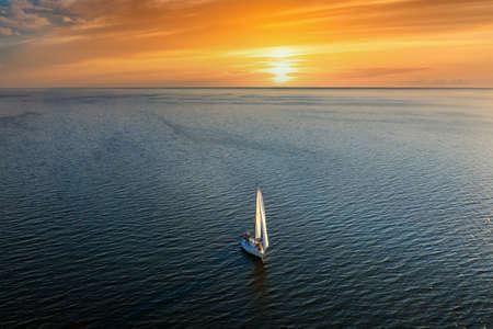 Yacht sailing at sunset. Luxury vacation at sea. Stock Photo