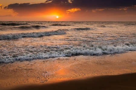 Sea waves on the background of the setting sun. Vacation at sea, Bali
