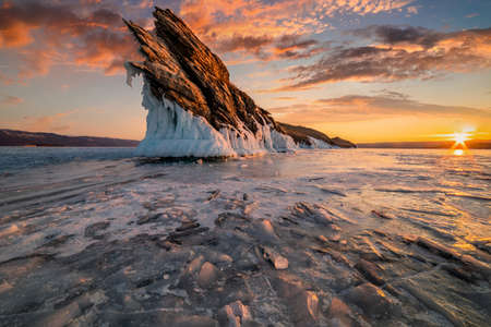 Rock on Lake Baikal in winter at dawn. Winter travel in Russia