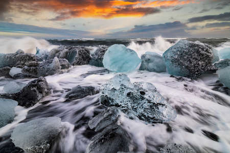 Ice rock and black sand at Jokulsarlon beach at sunset. Diamond beach in southeast Iceland.