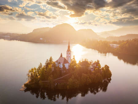 Bled Lake with Pilgrimage Church of the Assumption of Maria at sunrise. Aerial view.