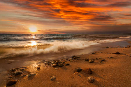 Sunset on the rocky shore of tropical sea. Summer vacation on tropical resort