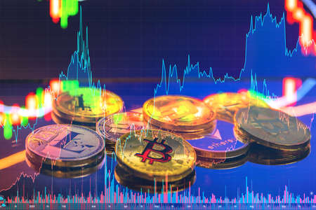 Bitcoin and cryptocurrency investing concept - Physical metal Bitcoin coins with global trading exchange market price chart in the background Stock Photo
