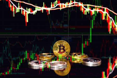 Bitcoin and cryptocurrency investing concept - Physical metal Bitcoin coins with global trading exchange market price chart in the background. Candle stick graph chart