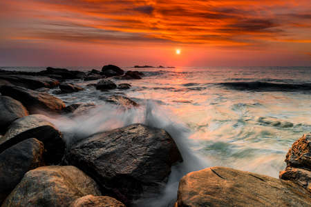 Sunset on the rocky shore of tropical sea. Stock Photo