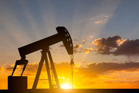 Oil pump at sunset background. Oil industry equipment. Stock Photo