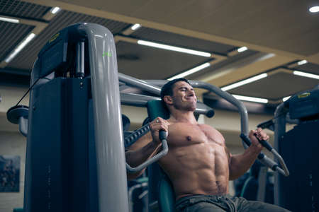 muscularity: heavy exercise. Sports Hall. Gym sports Guy bodybilder