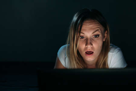 Image of young employer looking at laptop with surprise in badroom. Woman looking at pc screen against isolated black