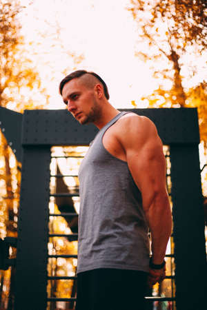 Young sexy athlete stands leaning on a wall bars in the park Imagens