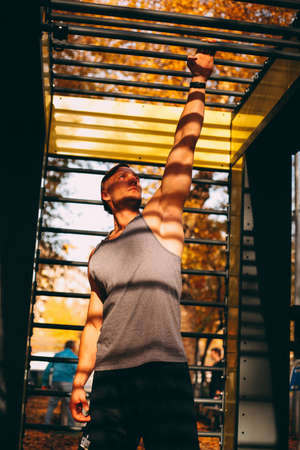Young sexy male athlete is training with monkey bars in the park