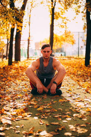 Handsome man squatting in autumn park in sportswear.