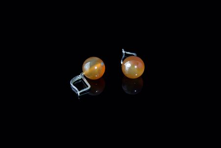 turbid: Beautiful earrings made of carnelian on a black background with a reflection in the glass Stock Photo