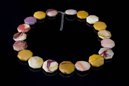 faceting: Beautiful, elegant necklace of multicolored agate stone on a black background. Stock Photo