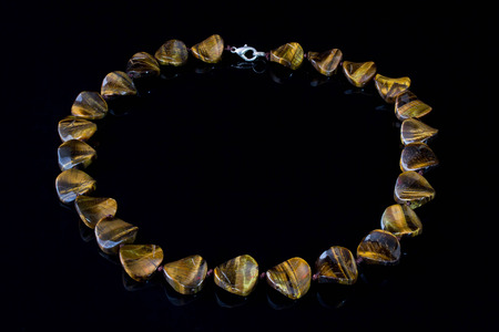 faceting: Beautiful, elegant necklace from cats eye stone on a black background. Stock Photo