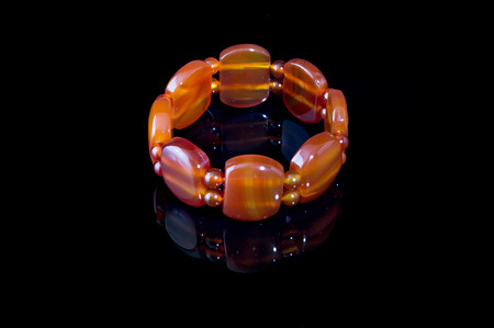 turbid: Beautiful bracelet made of carnelian on a rope, natural stone, orange on the black background, glass.