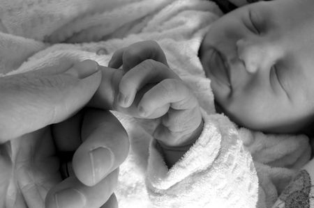 newborn girl holding on to her daddys finger while sleeping
