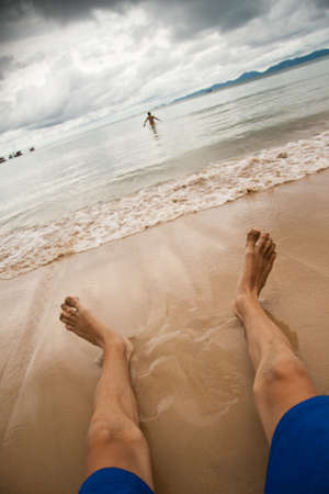 feet relaxing: image of the beach and the sea. Mens feet are on sand. water woman